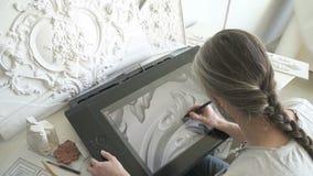 Restaurador do arquiteto que trabalha com a tabuleta gráfica que senta-se na tabela no escritório moderno video estoque