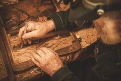 Restaurador superior que trabalha com elemento antigo da decoração em sua oficina Imagens de Stock Royalty Free