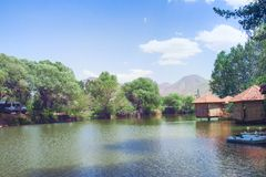 Restaurang Lchak, Yeghegnadzor, Armenien Sikt av ett damm, gazebos och berg Arkivfoto