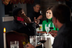 Restaurang: Mannen förargar andra, genom att använda mobiltelefonen under mål Royaltyfri Foto