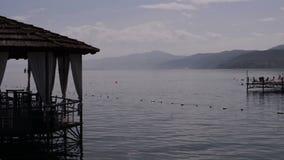 Restaurang som lokaliseras på sjön var folket kan tycka om på solnedgång arkivfilmer