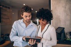 Restaurangaffärspartners som använder den digitala minnestavlan Arkivfoto