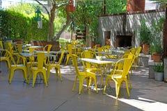 Restaurangborggård med gula stolar under träden royaltyfria bilder