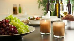 Restaurangbuffé med nya druvor, brännande stearinljus och ett vinexponeringsglas som postas på hyllan lager videofilmer