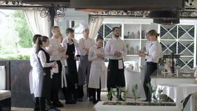 Restaurangchef och hans personal i terrass Växelverkan till huvudkocken i restaurang stock video