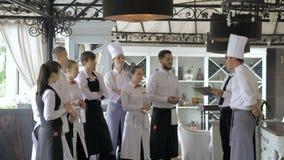 Restaurangchef och hans personal i terrass Växelverkan till huvudkocken i restaurang arkivfilmer