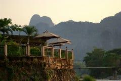 Restaurangen har en bakgrund av berg och solnedgången Arkivbild
