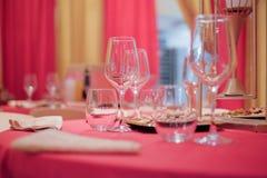Restauranginre - en tabell dekorerade med en röd bordduk in Royaltyfri Bild