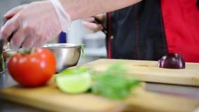 Restaurangkök En kock som klipper löken lager videofilmer