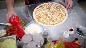 Restaurangk?k En kock som ?verst s?tter ost av pizza stock video