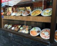 Restaurangmat shoppar in fönstret Arkivfoto