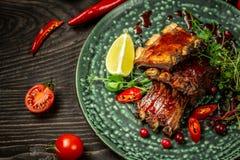 Restaurangmatbegrepp Grisköttstöd som grillas med BBQ-sås Smakligt mellanmål som tjänas som med gröna plantor på plattan Restaura royaltyfri bild