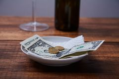 Restaurangspetsar eller drickspeng Sedlar och mynt på en platta arkivbild