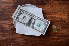 Restaurangspetsar eller drickspeng Sedlar och mynt på en platta royaltyfri fotografi
