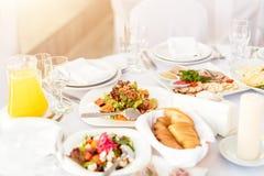 Restaurangtabell med mat Smakliga aptitretare, sallader Olika mål för gästerna på brölloptabellen arkivbild