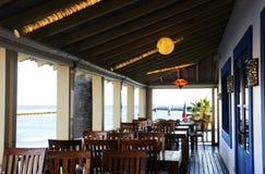 Restaurangterrass med sikt för blått vatten Arkivbild