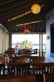 Restaurangterrass med trätabeller och stolar Arkivbild