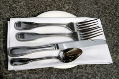 At the restaurant. Spoon, forks, knife, white napkin on marble table at the restaurant Stock Image