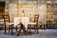 Restaurant. Table and chairs in front of historic wall - tuscany/italy Stock Images