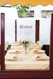 Restaurant. Outdoor bistrot table setting, flowers on table Royalty Free Stock Photo