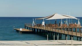 Restaurant auf dem hölzernen Pier des Meeres Leuteschwimmen und -aufstieg auf stoolmen Ein großes Zelt entwickelt sich im Wind stock video footage