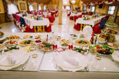 Restaurant banquet table served for celebration. Close-up on different food, glasses and plates. With blurred hall interior as background Royalty Free Stock Photography