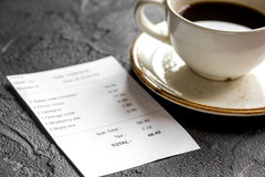 Restaurant bill, card and coffee on dark table background. Restaurant bill, credit card and coffee on dark table background stock photography