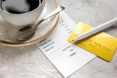 Restaurant bill, card and coffee on stone table background. Restaurant bill, credit card and coffee on stone table background stock photo