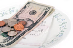Restaurant bill with dollar bills (tips) on a plate Stock Image