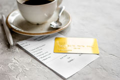 Restaurant bill paying by credit card for coffee on stone table background Royalty Free Stock Photo