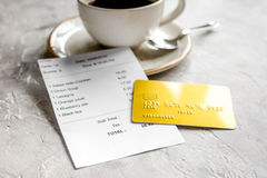 Restaurant bill paying by credit card for coffee on stone table background. Restaurant bill paying by credit card for cup of coffee on stone table background stock images
