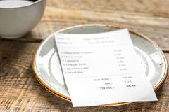 Restaurant bill paying by credit card for coffee on wooden table background Royalty Free Stock Image