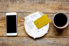 Restaurant bill paying by credit card and phone on wooden table background top view mock-up Stock Photo