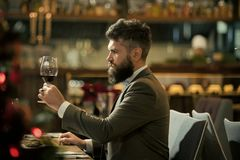 Restaurant blogger. Romantic dinner. young man standing and holding wineglasses.  royalty free stock photography