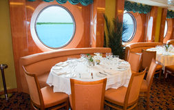 Restaurant on board a cruise liner. Restaurant on board a cruise ship ready for dinner with view from porthole Stock Images
