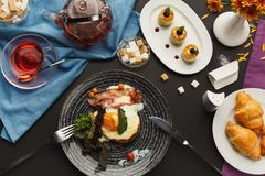 Restaurant breakfast with bacon and fried eggs. Restaurant delicious breakfast with sunny side up fried eggs, bacon, vegetables and greens, croissants and Stock Photo