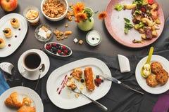 Restaurant breakfast with various sweet treats. Eating sweet restaurant breakfast with oatmeal cookies, croissants, yogurt, cheese pancakes, muesli, fresh Royalty Free Stock Image