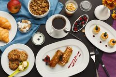 Restaurant breakfast with various sweet treats. Sweet restaurant breakfast with oatmeal cookies, croissants, yogurt, cheese pancakes, muesli, fresh berries and Royalty Free Stock Photo