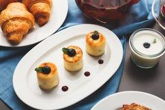 Restaurant breakfast with various sweet treats. Sweet restaurant breakfast with cheese pancakes, croissants, yogurt and freshly brewed tea served on black table Stock Image