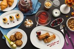 Restaurant breakfast with various sweet treats. Sweet restaurant breakfast with oatmeal cookies, croissants, yogurt, cheese pancakes, muesli, fresh berries and Stock Photo