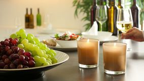 Restaurant buffet with fresh grapes, burning candles and a wine glass posted on the shelf. Restaurant buffet with fresh red and green grapes, two burning candles stock video footage