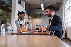 Restaurant manager having a conversation with chef. Restaurant business manager sitting and talking with chef. Restaurant owner having a conversation with Royalty Free Stock Photo