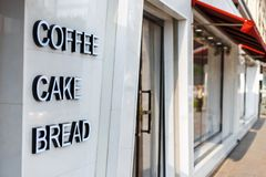 Restaurant cafe with door and window. Caption letters coffee, ca. Ke, bread. street stock photo
