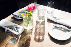 Restaurant on the canal Venice. Tulip in a vase. table setting for a lovey dinner. Empty glasses set in cafe. Part of. Table setting for a lovey dinner. Empty Stock Image