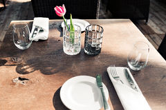 Restaurant on the canal Venice. Tulip in a vase. table setting for a lovey dinner. Empty glasses set in cafe. Part of. Table setting for a lovey dinner. Empty Stock Images