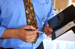 Restaurant check. This is a picture of a waiter holding a restaurant check Royalty Free Stock Images