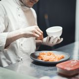 Restaurant Chef cook preparing salmon filet and crambling salad on the fish. royalty free stock photos