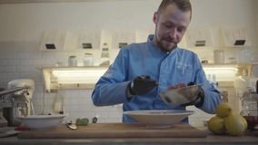 Restaurant chef putting in circular metal form a cutted tuna fish and making a round shape on the big plate. Beautiful. Dish decoration. Cook stand in the stock footage