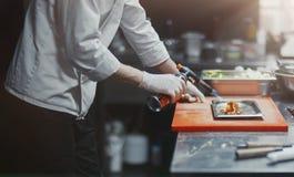Restaurant-Chefkoch, der Lachsleiste flambe in der offenen Küche vorbereitet lizenzfreie stockbilder