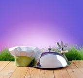 Restaurant cloche and chef's hat on a background of nature Stock Photography